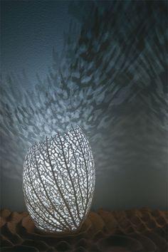 As luminárias Hyphae, de Jessica Rosenkrantz e Jesse Louis-Rosenberg, são projetadas algoritmicamente de forma individual e lembram corais. Não existem duas peças iguais. Cada luminária lança um padrão único de sombras ramificadas na parede e no teto, criando uma atmosfera etérea, orgânica e envolvente.