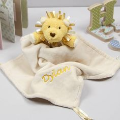 A super soft lion comforter blanket with ribbon tassels at the corners and the option to add personalised embroidery.Personalised embroidery can be added to make your gift unique. Tell us the name you would like and we'll do the rest. The embroidery is positioned in the corner of the blanket opposite the Lion in yellow embroidery thread. You can see our full range, including our personalised gifts, by clicking on our name (in blue) at the top of the page.Made from soft brushed cream fleece…