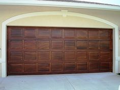 Painting faux wood grain on the garage door. Great idea!  Wonder if I could do it myself?