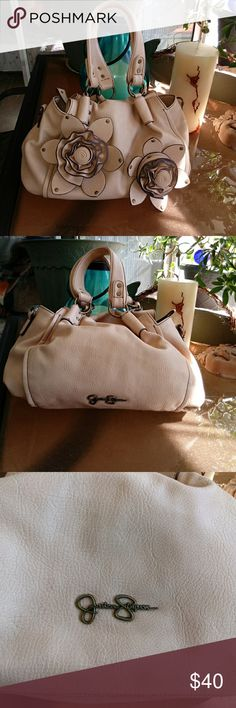Jessica Simpson Handbag Nice light latte color handbag has 2 large rosettes on front. Signature on back. Roomy CLEAN interior with one zippered pocket and 2 nice size pockets inside 14x9x6 COMES FROM SMOKE FREE, CAT FRIENDLY HOME. OPEN TO ALL REASONABLE OFFERS Jessica Simpson Bags