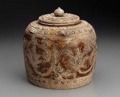 Covered Jar, Trân dynasty, 13th–14th century. Stoneware with cream and brown glazes, carved and punched decoration, molded and applied handles; 18.7 x 19 cm (7 3/8 x 7 1/2 in.). Gift of John D. Constable, 1989.755a-b. © 2016 Museum of Fine Arts, Boston