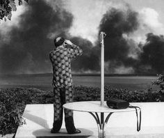 A pajama-clad man observes Japan's early morning surprise attack on the American naval base at Pearl Harbor, photographed by Baldwin H. Ward (December 7, 1941).