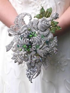 REF:233 ***NAME*** Silver asymmetric brooch bouquet ***DESCRIPTION*** A custom made unique shaped brooch bouquet handmade for you featuring leaves,roses and flowers with emerald accents. Please note bouquets will not be exactly the same as the photograph but extremely similar. ***SIZE