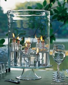 Outdoor lighting idea from Martha Stewart -gather clear apothecary bottles and fill them with lamp oil and wicks. Arrange the bottles under a large glass hurricane jar for protection and place on a sturdy glass cake stand. Apothecary Bottles, Wine Bottles, Small Bottles, Glass Bottles, Outdoor Parties, Garden Parties, Dinner Parties, Outdoor Entertaining, Deco Table