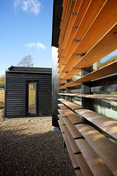 This house features blackened timber cladding and glazed walls shielded by wooden louvres.
