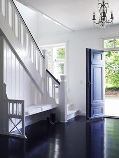Ebony door and floor, white staircase with built in bench