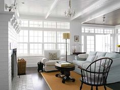All white living room with jute rug, painted brick fireplace, paneled ceiling.