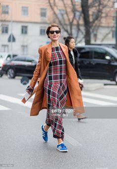 Konca Aykan wearing a checked dress, orange coat outside Fendi during Milan Fashion Week Fall/Winter 2017/18 on February 23, 2017 in Milan, Italy.