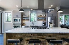 The kitchen mixes textures—strips of wood woven around the island, marble countertops, stainless steel appliances—for a look that's a little edgy, a lot cool.
