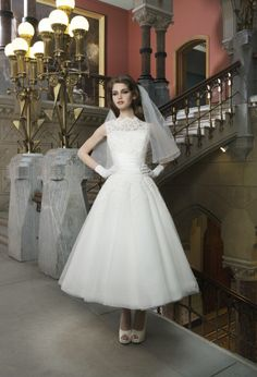 Justin Alexander wedding dress. Alencon lace and tulle tea length ball gown features a Sabrina neckline and silk dupion criss-cross pleated cummberbund. The back of the gown has a V-back neckline and silk dupion buttons. Available colors: Natural/Ivory