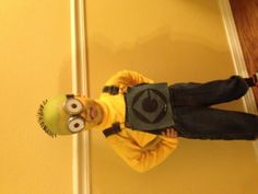 "Despicable Me Minion DIY costume Top- used a deflated ball and cut off some of the ""spikes"" and colored the ""hair"" black with a permanent marker.  Goggles- found some jar type things at hobby lobby and took the lids off them. Banded them together with elastic.  Then just put the rest together! Yellow paint, overalls, yellow turtle neck with a personalized ""Gru"" company logo!"