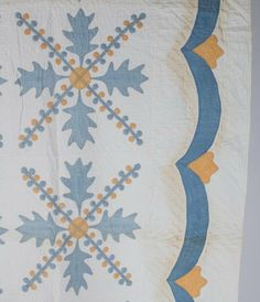 """SHENANDOAH VALLEY OF VIRGINIA """"OAK LEAF VARIANT"""" PIECED AND APPLIQUE QUILT, twenty 14"""" SQ blocks with faded blue and yellow solids encircled with cross-hatch hand stitching, each side with a swag border and double-line straight stitching, white backing. Third quarter 19th century. 75"""" x 83"""". Provenance: Collection of Jessie and the late Eugene Long, Broadway, VA."""