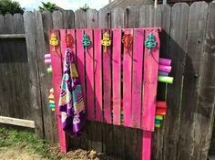 GENIUS! A painted pallet serves as a towel rack and pool noodle storage.  http://www.thatcomfyfeeling.com/video-organize-pool-toy-clutter-with-simple-diy-solutions/
