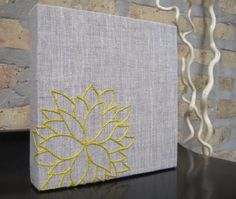 wrap a canvas in fabric and sew a cool design for diy artwork (I would actually use puff paint...)