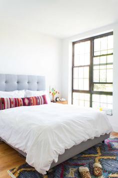 """On the all-white <a href=""""http://www.westelm.com/products/grid-tufted-upholstered-tapered-leg-bed-crosshatch-h1371/?pkey=cbeds"""" target=""""_blank"""">bed</a>, a tribal print <a href=""""https://the-citizenry.com/collections/pillows/products/baya-lumbar-pillow#.V0xTd5MrKCQ"""" target=""""_blank"""">pillow</a> really stands out."""
