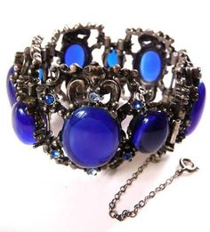 This is a Selro Renaissance Revival unsigned bracelet, and it is gargantuan.  This is a five panel bracelet cuff with huge dark blue cobalt glass cabs, and two panels are surrounded with six dark blue rhinestones, and three panels are surround with dark and light blue rhinestones.