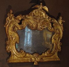 beautiful small #Italian mirror #Renaissance, late 16th century, #carved and gilded. Two angels on the sides and one on the bottom, a dove on a shell, and two faces of men in the arabesques. #Original #gilding and mercury mirror. Beautiful patina. For sale on Proantic by Antiques Provence.