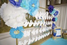 Blue and white paper flowers and cut out baby onesies for blessings for the baby. Fun baby shower activity! | Lovelyfest Event Design | Royal Blue Baby Shower