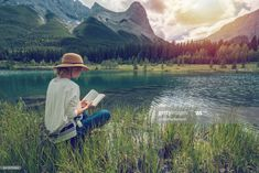 Stock Photo : Young woman reading a book by the lake