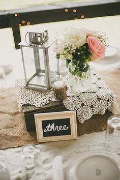 Vintage wedding centerpiece using a lantern, lace, a flower display, and a simple framed table number