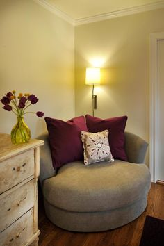 Plum accents in this cozy reading nook add drama to the neutral palette while the plush oversized chair and overhead lighting beckon readers to curl up with a good book. Meanwhile, contrasting shabby chic and modern styles in the space create a harmonious, relaxing vibe.