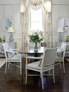 Love the sophistication of the drapes, chandelier, and hardwoods mixed with the white bamboo chairs and symmetrical hanging mirrors.