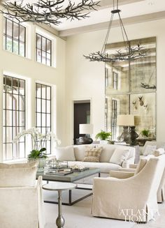 A pair of chandeliers by Darren Hardeman evoke winter branches and hang over an arrangement of low-maintenance upholstered seating in the living room designed by Richard Tubb.