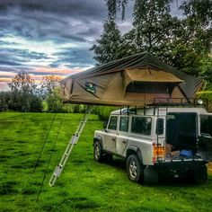 White Land Rover Defender with a Howling Moon roof tent set-up