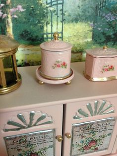 Add a special touch to your mini kitchen. bakery or tearoom with this adorable, authentic mini reproduction of a 3-PieceTea Caddy, also used as a Biscuit Barrel. This cutie is painted in shabby pink with golden accents and embellished with a pretty vintage roses with and sits on a salver.  Cover is removable. Lead-free Nickel-free Metal.  Price is for one 3 piece Round Tea Caddy. Other accessories shown sold separately.  Dollhouse Miniature 1/12 scale  Not a toy. Collector item. not reco...