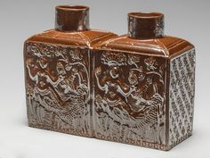 English double tea caddy decorated with mermaids ustrous brown salt-glazed stoneware, moulded, height, whole, 13cm, dated 1770. Production place: Derbyshire. Rococo.
