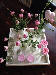 Voorjaar op tafel! Roze ranonkels, gerbera's en kaarsjes.