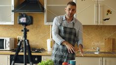 Young handsome man in apron shooting video food blog about cooking on dslr camera in kitchen. Food