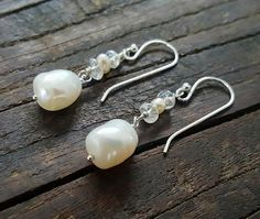 An elegant set of earrings that can be worn for a wedding or any special occasion. I used sterling silver wire and ear hooks to highlight the pretty freshwater pearl and quartz beads. Featured are natural baroque pearls in an ivory or off white colour. - Materials: Sterling silver, natural pearls, pearlized quartz. - Measurements: 1.5 inches or 4 centimetres. - A matching bracelet is available, please click on the link to view. https://www.etsy.com/ca/listing/5198...