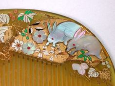 Bekko kushi comb with inlaid mother-of-pearl and gold and coloured enamel. Very delicate motifs of rabbits, leaves and flowers.