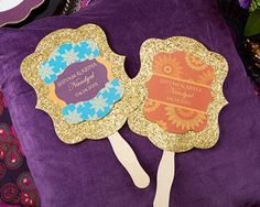 """We're definitely """"fans"""" of these beautiful Indian-inspired gold hand fans, perfect for completing the look of your jewel tone wedding or bridal shower decorations. Hand fans are personalized and feature gold glitter on one side and gold cardstock on the o"""