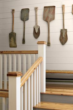 In this Georgia cabin, an array of vintage Swedish snow shovels hangs on the landing's plank wall. Large utilitarian objects like these can offer a striking way to fill a blank wall.