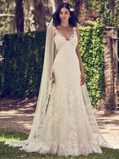 Maggie Sottero - CHARLOTTE, Embroidered lace motifs cascade over tulle in this sheath wedding dress, completing the bodice, illusion V-neckline, illusion straps, and illusion back. Finished with covered buttons over zipper closure. Tulle veil with lace edging sold separately.