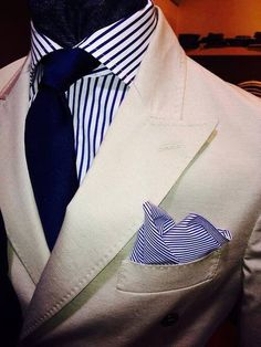 Beige jacket with peak lapels, white shirt with navy candy stripes, navy tie