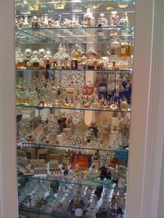 Perfume bottles on shallow glass shelves with mirror behind them. Of course it does not have to be perfume, just glass bottles with colored water. Pretty !