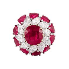 Platinum, Ruby and Diamond Cluster Ring   Centering one cushion-shaped ruby approximately 4.40 cts., encircled by 10 marquise-shaped diamonds approximately 4.75 cts., further edged by 10 pear-shaped rubies approximately 5.50 cts., the tapered shank pave-set all around with small round diamonds, approximately 9.3 dwt.