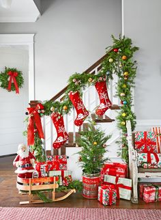 A Christmas staircase filled with garland, stockings, presents, and a tiny tree.
