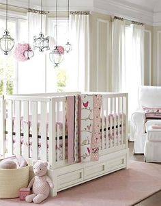 The right furniture choices can unlock the potential of a smaller room. This crib has a slim profile and drawers that make smart storage space beneath. Bedding in tonal pinks and browns with a mix of stripes, polka dots and birdies is sweet and whimsical. Cast-iron decorative pendants hung from the ceiling add a touch of princess-castle charm and are a pretty alternative to a mobile near the crib.