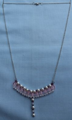 """This necklace has a row of pink transparent beads with white pearl and transparent beads. It also features purple seed beads on a silver plated chain. 58.5cm (23"""").  Materials used: Glass, acrylic and a silver plated chain."""
