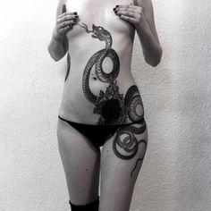 A dark hypnotizing side and torso tattoo by Alexander Grim.
