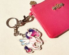 Take this adorable mythical unicorn to travel with you wherever you go!  The charm is made of clear acrylic, and measures approx. 2 in. x 1.5 in. (5.08 x 3.81 cm). Charm is waterproof with this cute unicorn printed on both sides.  Makes a great gift for friends and family, or as a gift to yourself and wear them on your backpack, purse, camera, planners, game consoles & more =) Choose between keychain, cell phone strap, or dust plug (strap included) attachment to the unicorn charm. Ph...