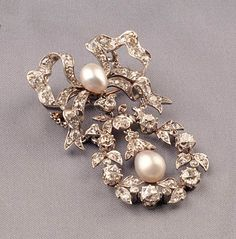 Edwardian Platinum Pearl, and Diamond Pendant/Brooch, designed as a bow suspending a garland motif, set throughout with old mine-cut diamonds, and two pearls, approx. total diamond wt. 6.37 cts., lg. 2 1/2 in.,