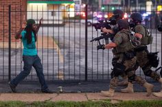 Images of police confronting an unarmed black man protesting the fatal shooting of Michael Brown have been going viral. | Images Of Ferguson Police In Riot Gear Confronting An Unarmed Man Go Viral