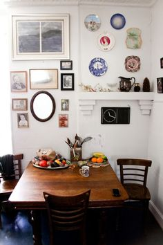 Great way to display a collection of vintage treasures: mirrors, photos + plates all together.