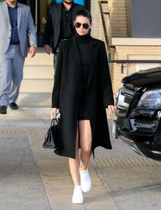 While out shopping in Los Angeles, Kendall Jenner borrows Kim Kardashian West's signature look of a body-con dress under an overcoat. The model stepped out in a leggy look pairing a black turtleneck mini with white sneakers.