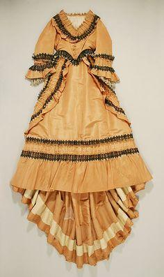 1863-1864 Gold silk 2-piece tea gown with black & blonde lace trim.